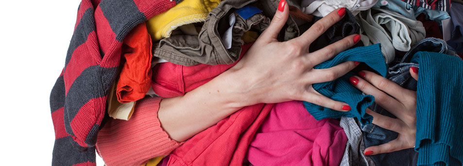 Woman-holding-a-huge-pile-of-clothes.jpg